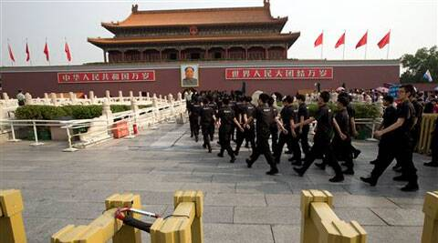 Security guards march onto a bridge in front of Tiananmen Gate in Beijing, where a man crashed an SUV and set the vehicle on fire after driving through a crowd of tourists. (Source: AP)