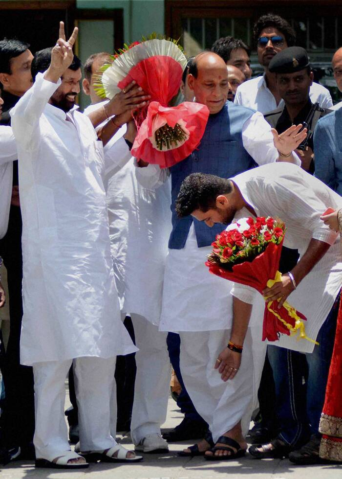 Ram Vilas Paswan flashes victory sign as his son Chirag Paswan seeks blessings of Rajnath Singh at his residence in New Delhi on Monday. (Source: PTI)
