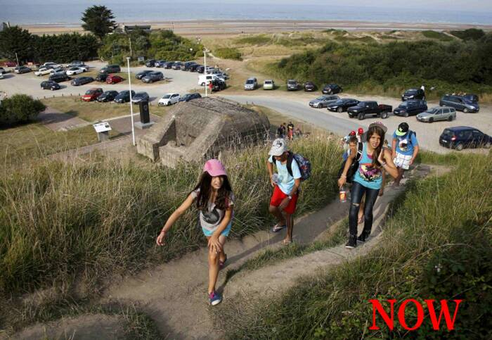 Youths hike up a hill past an old German bunker overlooking the former D-Day landing zone of Omaha Beach near Colleville sur Mer, France, August 23, 2013. (Source: Reuters)