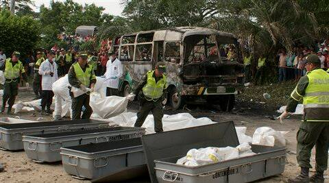 Police carry bags containing the remains of children who burned to death in the bus parked behind in Fundacion in northern Colombia. (AP Photo)