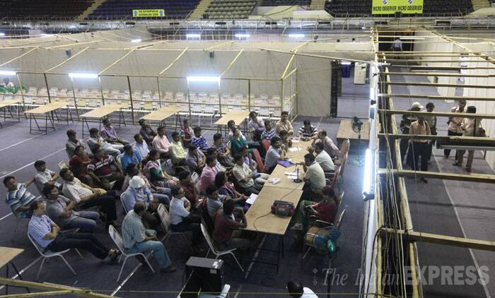 Polling personnel are seen being instructed about the counting process a day ahead of vote counting at Netaji Indoor stadium in Kolkata on Thursday. (Source: Express photo by Partha Paul)