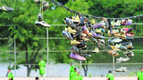 "Discarded soccer boots hang from an electric wire where they were thrown by their owners over several months after Sunday ""pelada""matches in the Morro do Papagaio favela in Belo Horizonte, a World Cup host city. ( Source: Reuters )"