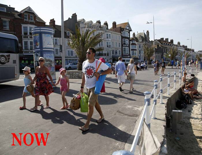 Tourists walk along the beach-front in the Dorset holiday town of Weymouth, England. (Source: Reuters)