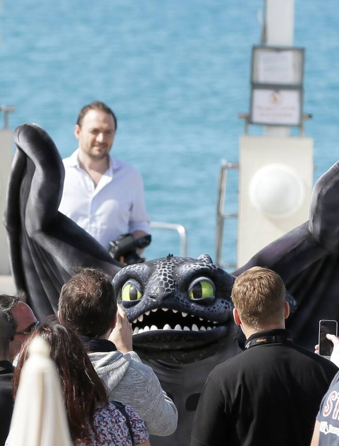 Tourists take a closer look at Toothless, the giant dragon from 'How to Train You Dragon 2'. (Source: AP)