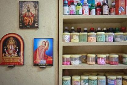Pictures of Hindu gods hang beside a medicines rack inside a clinic in Pune (Reuters)