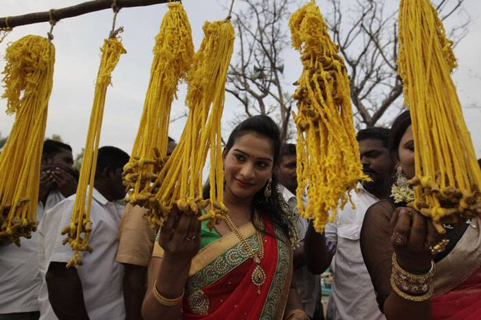 A eunuch looks at holy strings displayed at a temple premise during the annual eunuch festival in Koovagam. (AP)