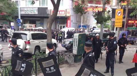 police officers stand guard near a blast site which has been cordoned off, in downtown Urumqi, capital of northwest China's Xinjiang Uygur Autonomous Region, Thursday, May 22, 2014. (AP photo)