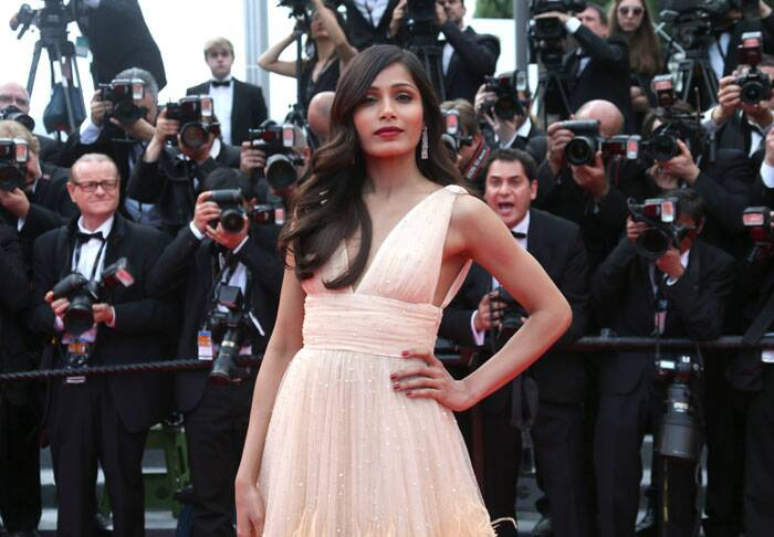 Side-parted soft wavy hair and vibrant red lips went very well with Freida's dress. (Source: AP)