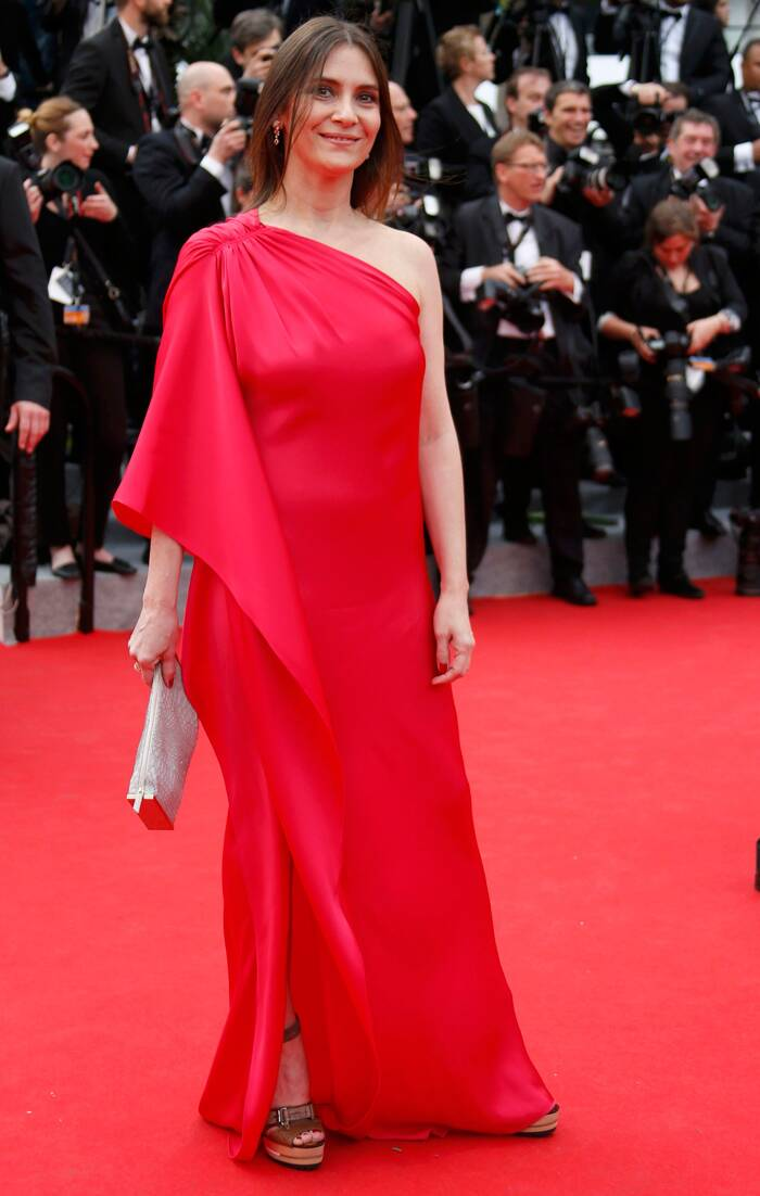 French actress Geraldine Pailhas matched the carpet in a one-shoulder flowy dress with ankle-strapped heels. <br /><br /> Seen here, the actress smiles as she poses for the photographers on the red carpet as she arrives for the opening ceremony of the 67th Cannes Film Festival and the screening of the 'Grace of Monaco'. ( Source: Reuters )