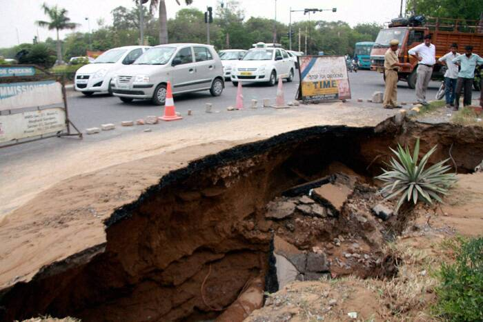 A large portion of road caved in at Atul Kataria crossing due to the leakage of a water pipeline in Gurgaon. ( Source: PTI )