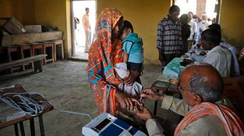 A polling official marks a finger of a woman with indelible ink before she casts her vote. (Source: AP)
