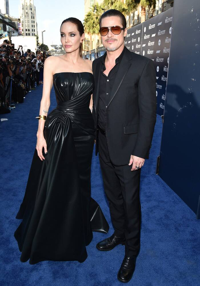 Hollywood actress Angelina Jolie weaved black magic in a strapless leather gown at the world premiere of 'Maleficent' in Los Angeles  on Wednesday (May 28). Dark eyes, sleek ponytail and golden spikes bracelet finished off her look.<br /> Meanwhile, her fiance Brad Pitt also complimented Jolie in an all black avatar. <br />Angelina Jolie and Brad Pitt pose for the photohgs at the premiere (Source: AP)