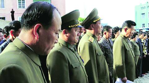 North Korean officials stand among the families of the victims of a building collapse. AP