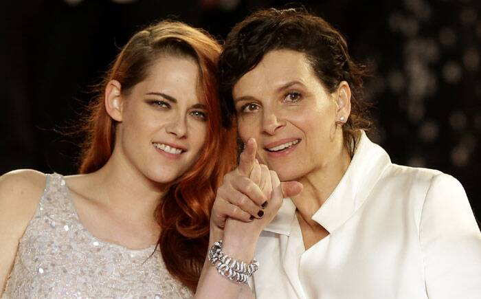 Kristen Stewart and co-star Juliette Binoche hold hands as the cameras snap away. (Source: AP)