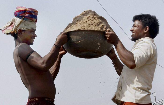 Two labourers lift a sand basket on the occasion of May Day or International Labour Day on the river bank of Yamuna in Allahabad. (PTI)