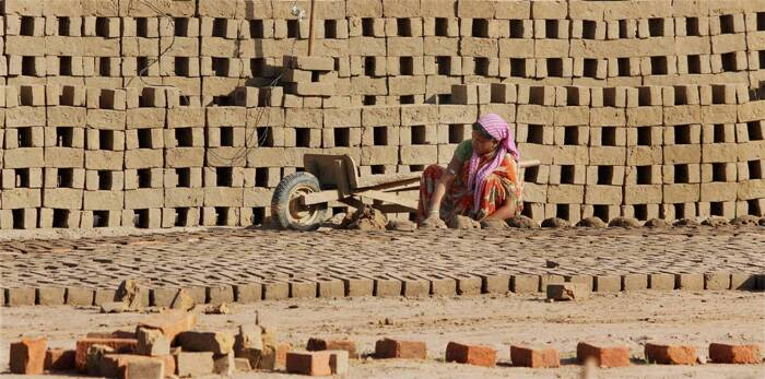 A laborer works at a brick factory on the outskirts of Jammu on Labour Day. (PTI)