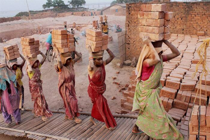 Female workers carry bricks on their heads at Jirania on the outskirts of Agartala on International Labour Day. (PTI)