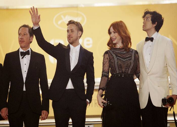 Ryan Gosling waves to fans as he poses for pictures along with Reda Kateb, actress Christina Hendricks and her partner Geoffrey Arend. (Source: AP)