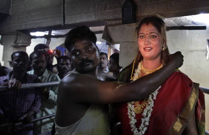 A temple priest ties a holy string around the neck of a eunuch as a ritual signifying marriage to warrior-god Aravan in Koovagam. (AP)