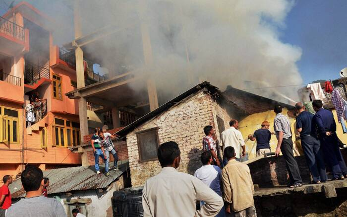 People trying to douse a fire that broke out in a house due to leakage of a gas cylinder in Mandi, HP on Monday. (Source: PTI)