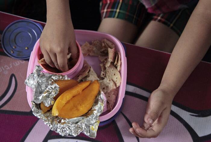 A schoolgirl enjoys her slice of mango during her lunch break in school in Jammu. (AP)