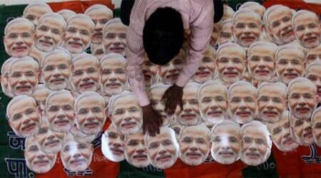 BJP worker preparing the mask of Narendra Modi for counting day celebration at Lalbaug on Wednesday. (Source: Express photo by Prashant Nadkar)