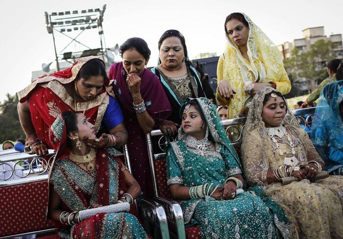A bride speaks to her relative as they wait for the start of their mass marriage ceremony. (Reuters)