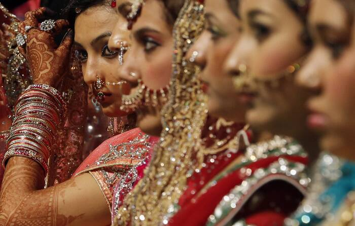 Brides sit during a mass marriage where thirty-five couple got married in Mumbai. (AP)