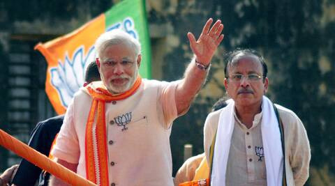 BJP PM candidate Narendra Modi waves during an election road show in Varanasi on Thursday (Photo: PTI)