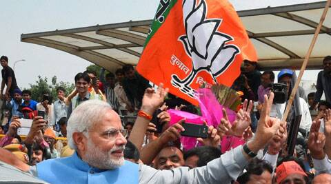 Narendra Modi waves victory sign to the cheering crowd on his arrival at the IGI Airport in New Delhi on Saturday. ( Source: PTI )