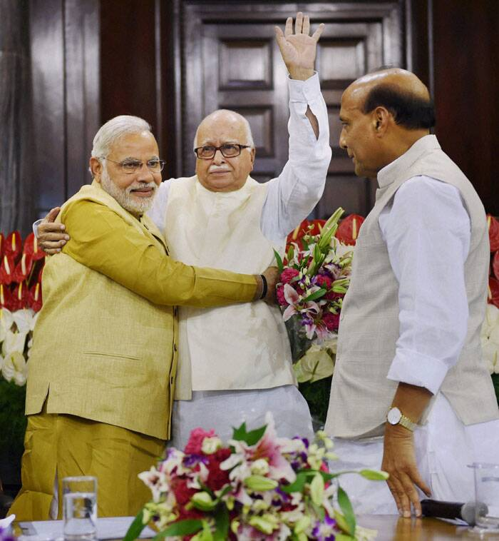 Prime Minister-elect Narendra Modi hugs an emotional LK Advani as Rajnath Singh looks on during the BJP parliamentary party meeting at the Central Hall of Parliament in New Delhi on Tuesday. (Source: PTI)