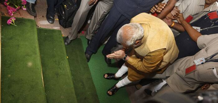 Narendra Modi declared that the Lok Sabha election results represents a new hope for the common man and dedicated his government for the uplift of the poor, oppressed and deprived. <br /> Narendra Modi, bends down with folded hands on the steps of the Central Hall as a sign of respect as he arrives for the BJP parliamentary party meeting in New Delhi. (Source: PTI)