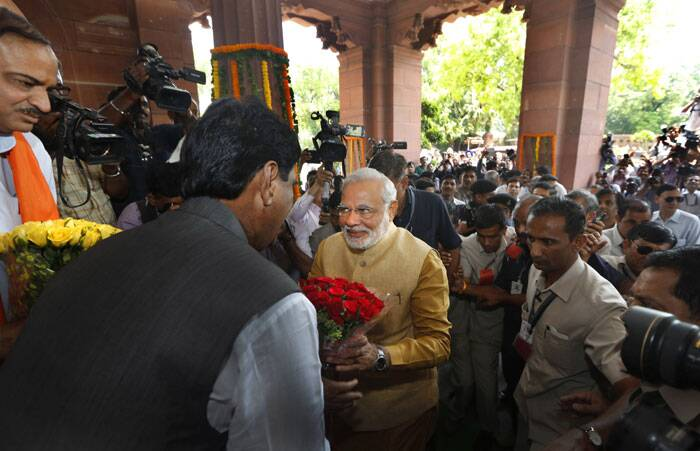 Narendra Modi, center, is received with flowers as he arrives for the BJP parliamentary party meeting in New Delhi. (Source: AP)