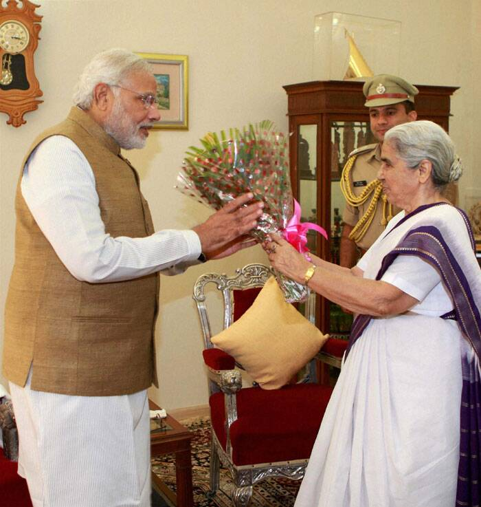 Gujarat Governor Kamla Beniwal presents a bouquet to Prime Minister-elect and outgoing Chief Minister Narendra Modi after the latter submitted his resignation in Gandhinagar on Wednesday. (Source: PTI)