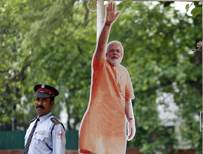 As challenger Modi sought a personal mandate in Varanasi, crowning his campaign to rule the country with a mix of pro-business policies and Hindu nationalism.<br />A private security guard stands next to a cut-out of Hindu nationalist Narendra Modi, the prime ministerial candidate for BJP, outside the party's office in New Delhi. (Source: Reuters)