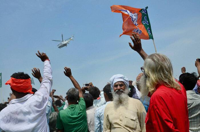 People wave to the chopper of BJP Prime Ministerial candidate Narendra Modi as he leaves after an election campaign rally in Faizabad. (PTI)