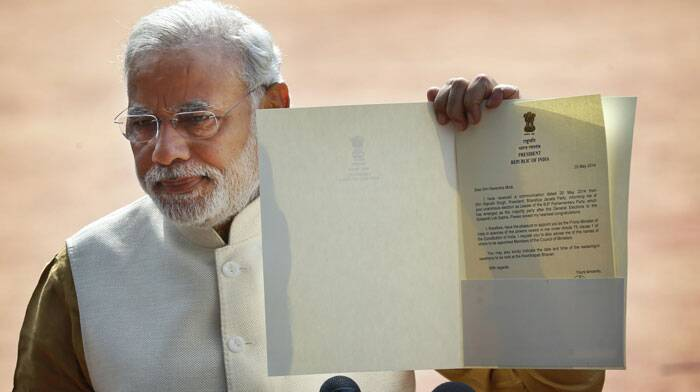In his brief interaction with the media outside Rashtrapati Bhawan, Modi displayed the President's letter appointing him to the top post. (Source: PTI)