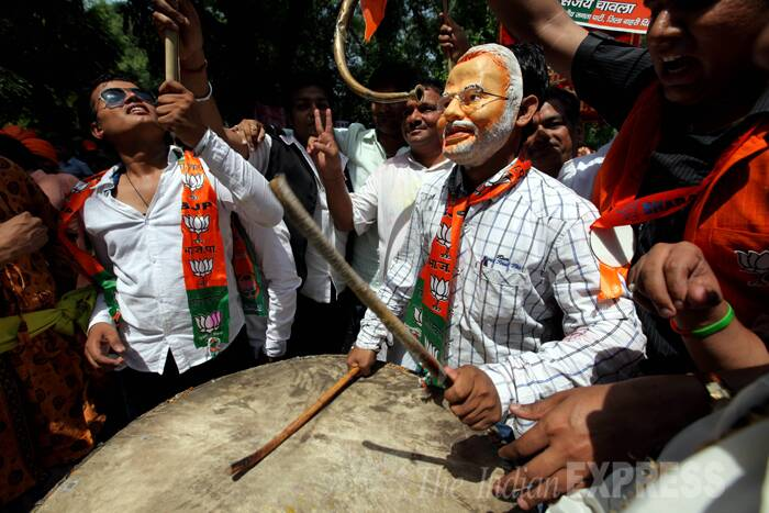 Men wearing Modi masks celebrating. (Source: Express Photo by Ravi Kanojia)