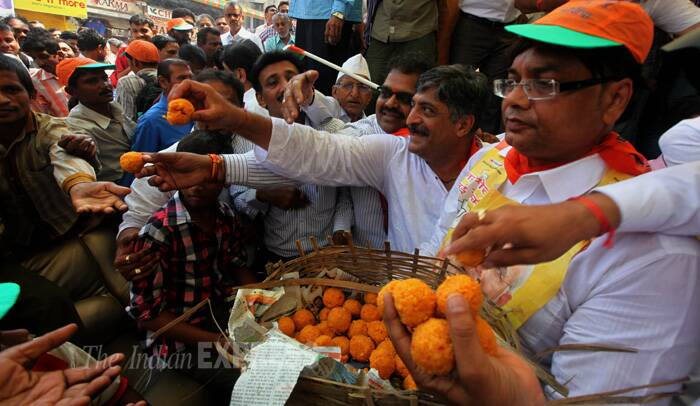 BJP party workers distribute sweets during the celebrations. (Source: Express photo by Prashant Nadkar)