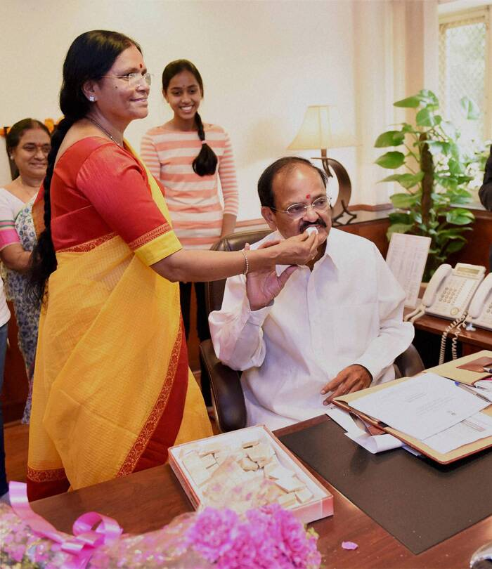 Venkaiah Naidu being offered sweets by his  wife M. Ushamma after he takes charge of the Urban Development and Housing Ministry. (Source: PTI)