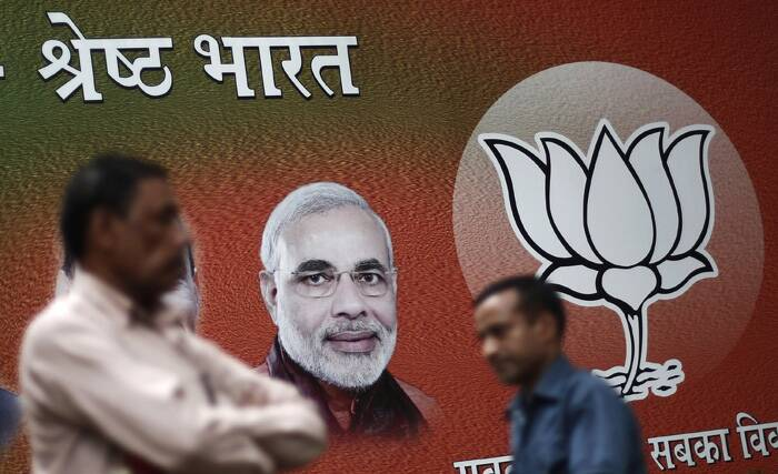 "The rupee and stocks surged as investors bet Modi will usher in a stable government focused on reviving Asia's third-largest economy. <br />Men walk past a hoarding of Narendra Modi outside the party headquarters in New Delhi. The hoarding reads, ""Excellent India"".  (Source: Reuters)"