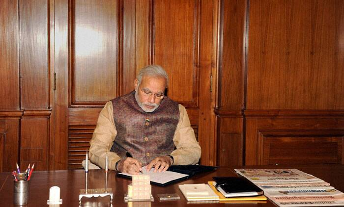 Prime Minister Narendra Modi takes charge of the office at PMO in New Delhi on Tuesday. (Source: PTI)
