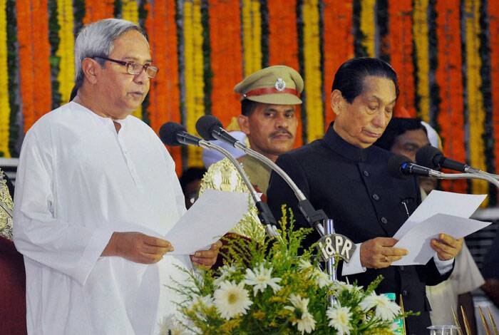 Also sworn in were 21 ministers, including eight fresh faces as five members of the previous ministry were dropped. <br /> Naveen Patnaik is sworn-in as Chief Minister of Odisha by the Governor SC Jamir during a ceremony at Rajbhawan in Bhubaneswar on Wednesday. (Source: PTI)