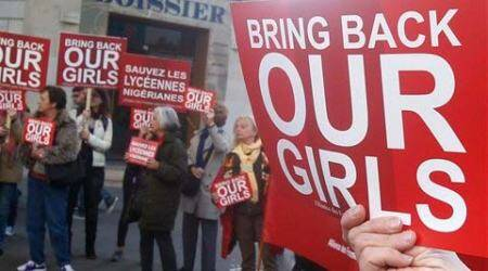 A Woman holds a sign during a rally near the Nigerian embassy to raise to show support for the release of the kidnapped girls in Nigeria in Paris on Monday. (Source: AP)