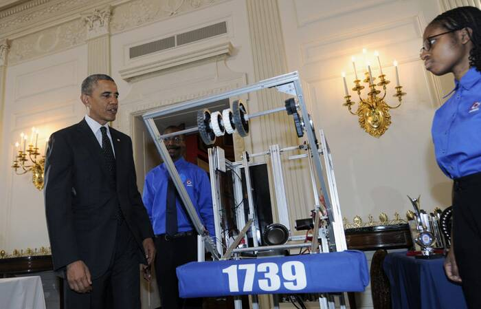 President Barack Obama seems intrigued as he looks at a robot by John Moore (19), center, and Lydia Wolfe (18) from Chicago. <br /><br /> The science exhibition that took place in the Dining Room at the White House displayed projects by winners from the field of science, technology, engineering and math (STEM) competitions from across the country. (Source: AP)