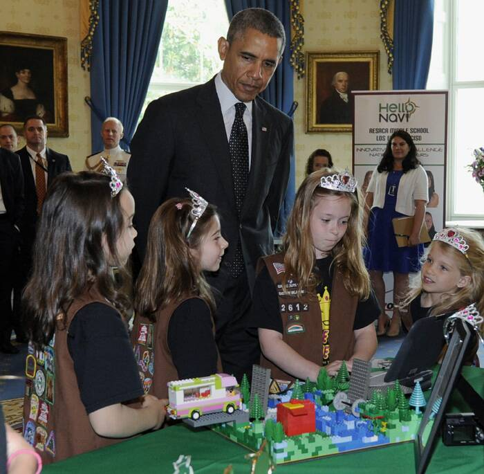 The President examines the girls' flood-proof bridge as he had a look at the different science projects on display at the 2014 White House Science Fair. (Source: AP)
