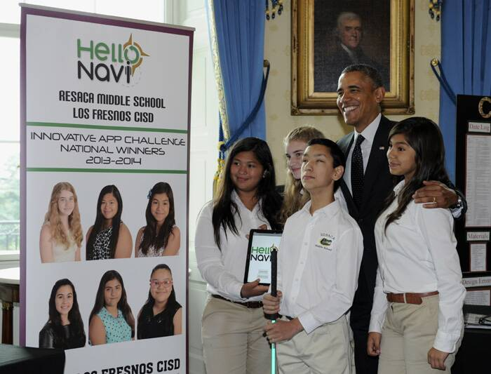 The President smiles widely as he posed for a group picture with students from Los Fresnon, Texas. The students show off their creation – an app that helps visually challenged students navigate their school. (Source: AP)