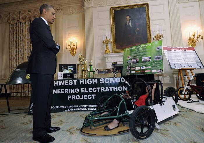 "President Barack Obama looks serious as he speaks to Deidre Carillo (18) from San Antonio, Texas, as she sits in her electric car. The Presient took the initiative of launching the exhibition so as to encourage women to take up science. ""There's so much talent to be tapped if we're working together,"" he said at the fair. (Source: AP)"