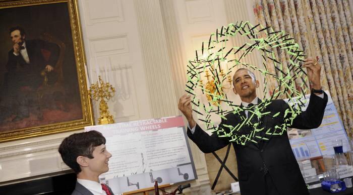 President Obama examines a model that demonstrates how polymers expand, as he talks with Peyton Robertson (12) of Ft. Lauderdale. (Source: AP)