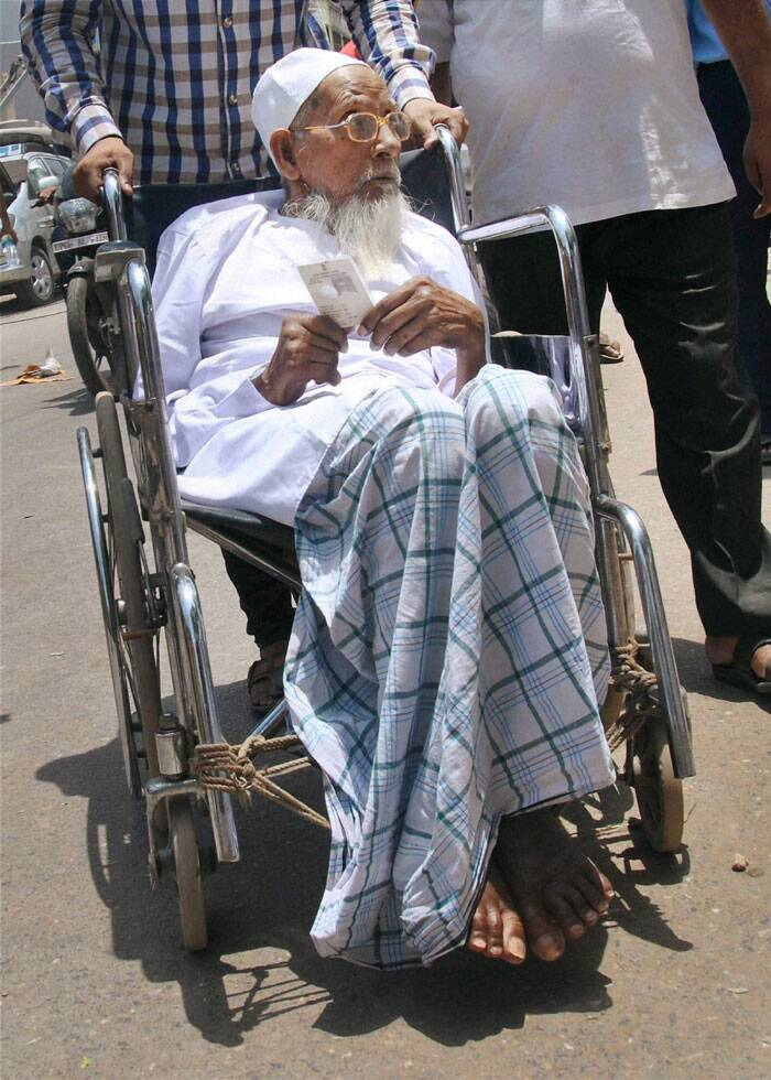 An old voter arrives to cast his vote for Lok Sabha polls in Varanasi on Monday. (PTI)